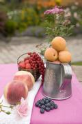 Peaches, apricots & fresh berries on table out of doors Stock Photos