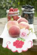 Fresh peaches and berries on table out of doors Stock Photos
