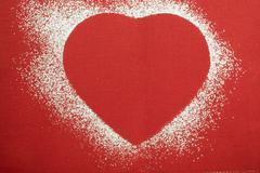 Red heart shape outlined in icing sugar Stock Photos
