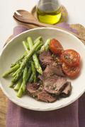 Beef with green asparagus and tomatoes Stock Photos
