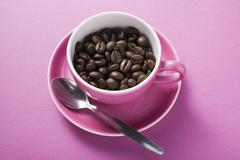 Coffee beans in pink coffee cup with spoon in saucer Stock Photos
