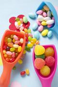Assorted coloured sweets in plastic scoops Stock Photos