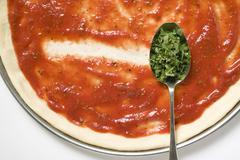 Pizza base with tomato sauce & spoonful of oregano (close-up) Stock Photos