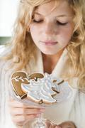 Blond girl holding glass bowl of assorted gingerbread biscuits Stock Photos