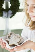 Blond girl holding assorted gingerbread biscuits on napkin Stock Photos