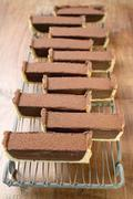 Rectangular chocolate tart with cocoa powder (in pieces) Stock Photos