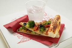 Two pieces of American-style vegetable pizza & mineral water Stock Photos