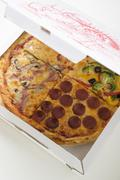 US-style ham, pepperoni & vegetable pizza in quarters Stock Photos