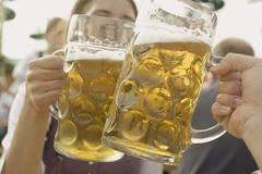 Hands clinking two litres of beer together (Oktoberfest, Munich) Stock Photos