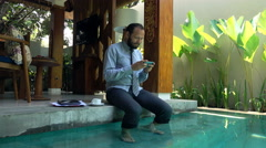 Young businessman using smartphone sitting by pool in outdoor villa Stock Footage