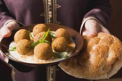 Woman serving falafel (chick-pea balls) with flatbread Stock Photos