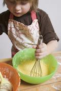 Small boy stirring cake mixture with whisk Stock Photos