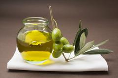 Green olives on twig beside jar of olive oil Stock Photos