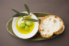 Green olives on twig in bowl of olive oil, white bread Stock Photos