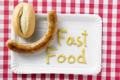 Sausage with bread roll and 'Fast Food' written in mustard Stock Photos