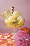 Ice cream sundae with fresh fruit, cocktail umbrella Stock Photos