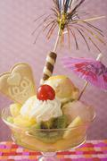 Ice cream sundae with fresh fruit and cocktail umbrella Stock Photos