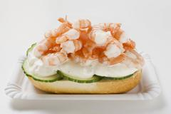 Roll topped with shrimps, cucumber and remoulade Stock Photos