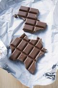 Bar of chocolate, partly eaten, on silver paper Stock Photos