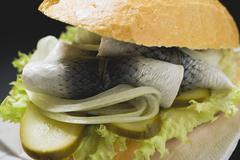Herring, onions and gherkins in bread roll (close-up) Stock Photos