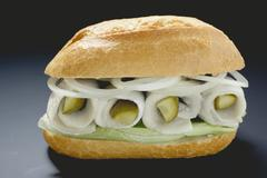 Herring, onions and gherkins in bread roll Stock Photos