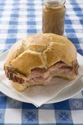 LeberkŠse in roll, partly eaten, on plate, jar of mustard behind Stock Photos