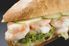 Bread roll filled with shrimps, cucumber and remoulade Stock Photos