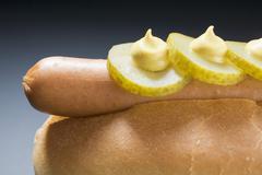Hot dog with gherkins and mustard (close-up) Stock Photos