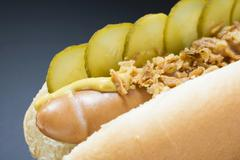 Hot dog with gherkins, fried onions and mustard (close-up) Stock Photos