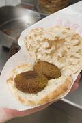 Hand holding pita bread filled with falafel (chick-pea balls) Stock Photos