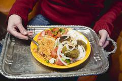 Person holding falafel with accompaniments on tray (N. Africa) Stock Photos