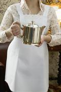 Chambermaid holding silver pot Stock Photos