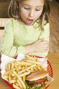 Horrified girl looking at hamburger and chips Stock Photos