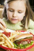 Girl eating chips with ketchup and hamburger Stock Photos