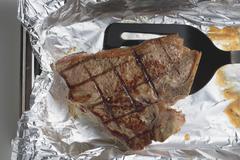 Grilled T-bone steak on aluminium foil with spatula Stock Photos