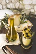 Olives, olive oil, cheese & crackers on table out of doors Stock Photos