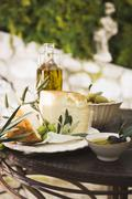 Cheese, olives and olive oil on table out of doors Stock Photos