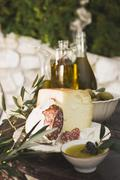 Cheese, salami, olives and olive oil on table out of doors Stock Photos