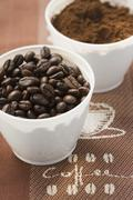 Coffee beans and coffee powder in two beakers Stock Photos