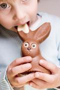 Child biting into chocolate Easter Bunny Stock Photos