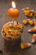 Cupcake with pumpkin candle & candy corn for Halloween (USA) Stock Photos