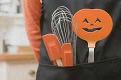 Kitchen tools for Halloween in an apron pocket Stock Photos