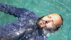 Businessman with closed eyes floating on water in pool, super slow motion 240fps Stock Footage