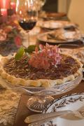 Pecan pie on table laid for Thanksgiving (USA) Stock Photos