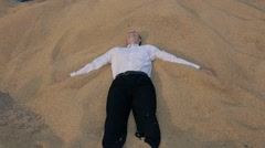 The young man in white shirt falls on the pile of grain on the back. Stock Footage