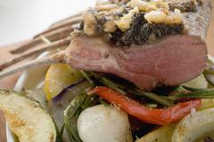 Rack of lamb with pesto crust and pine nuts on vegetables Stock Photos