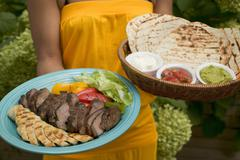 Woman serving Asian platter and basket of accompaniments Stock Photos