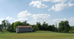 Old Barn on Farmers Field with Rolling Hills and Trees 10bit, 4K Stock Footage