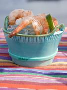 Cooked shrimps on ice cubes in blue dish Stock Photos