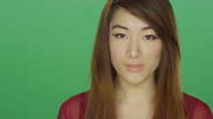 Young Asian woman shyly staring, on a green screen background Stock Footage